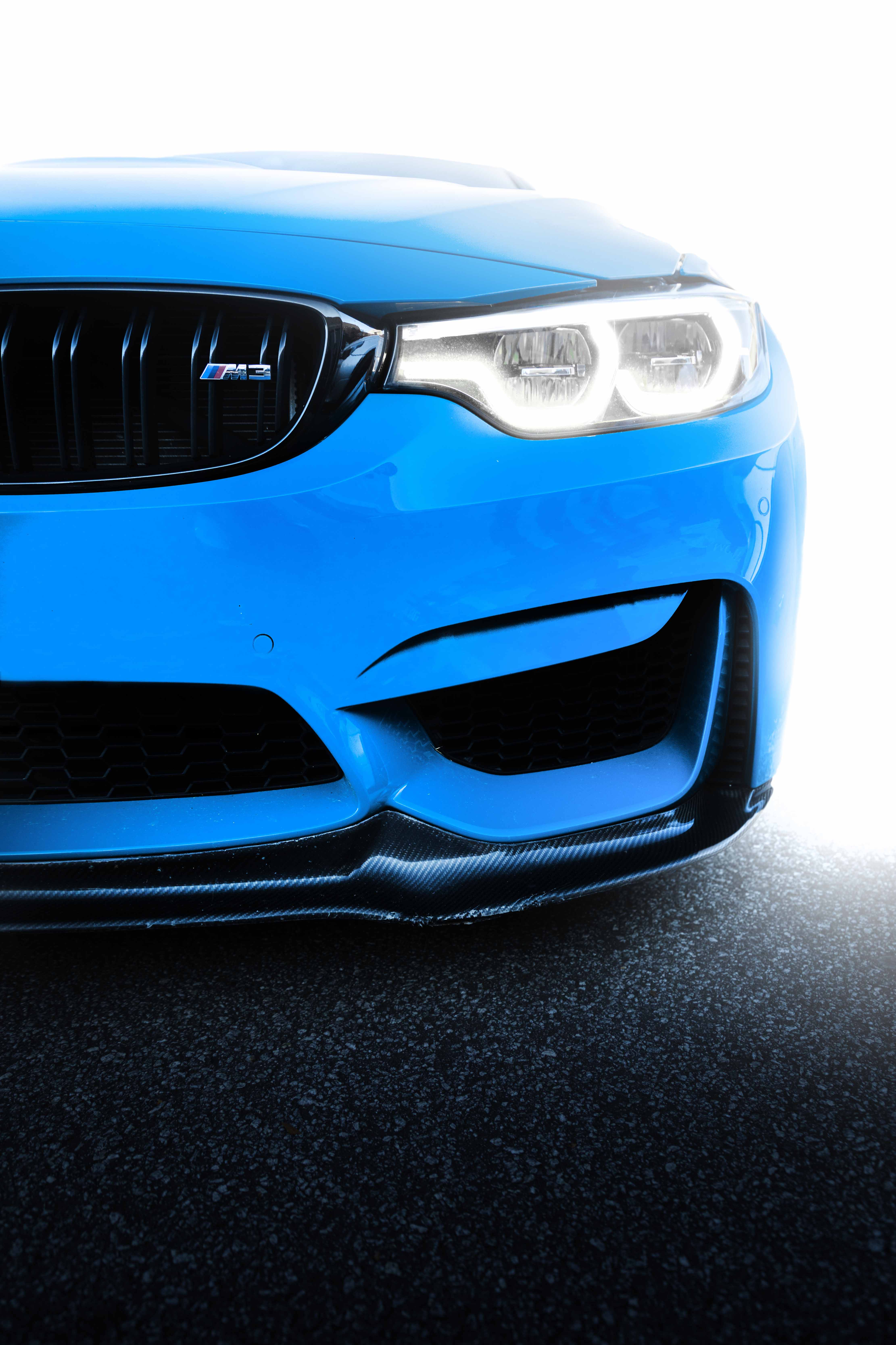 Blue BMW M3 with headlights on